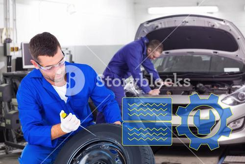 Composite image of mechanic working on tire over white background