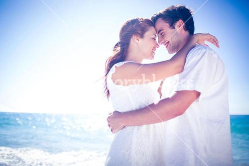 Happy couple hugging at the beach