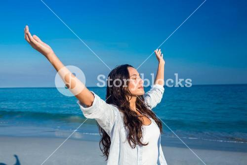 Happy woman with eyes closed at the beach