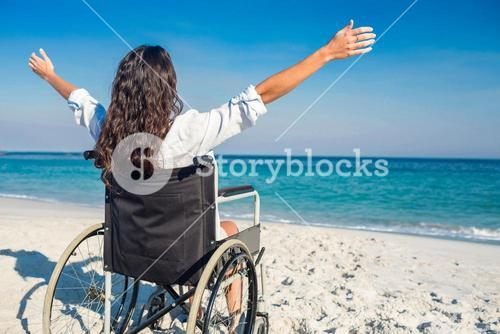 Disabled woman with arms outstretched at the beach