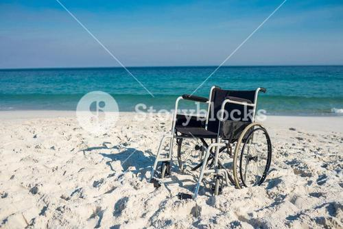 Black wheelchair on the beach
