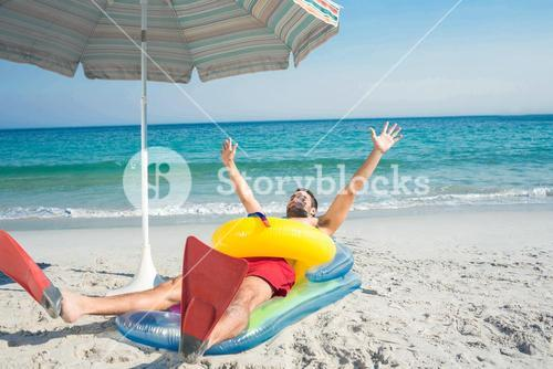 Man lying on the beach with flippers and rubber ring