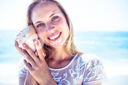 Lovely woman listening to a shell