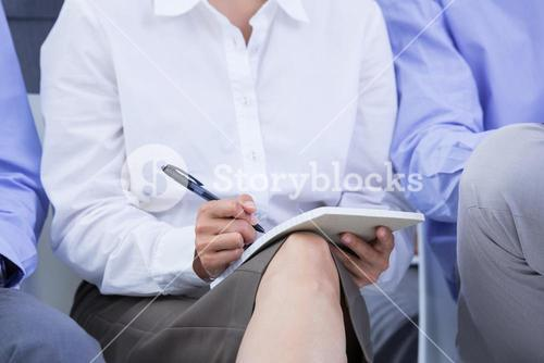 businesswomen taking a note during a meeting