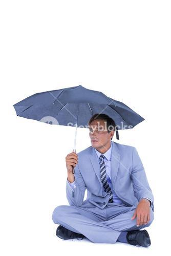 Businessman sheltering under umbrella