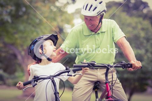 Happy grandfather with his granddaughter on their bike