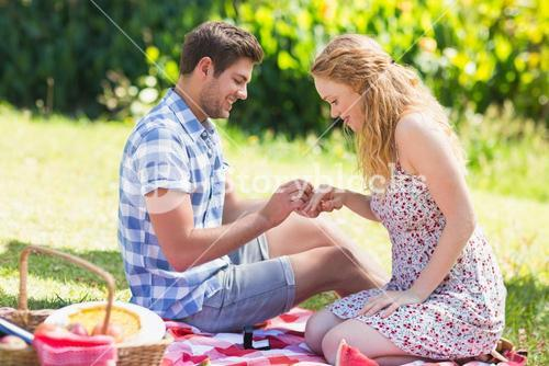 Young man putting on ring during marriage proposal
