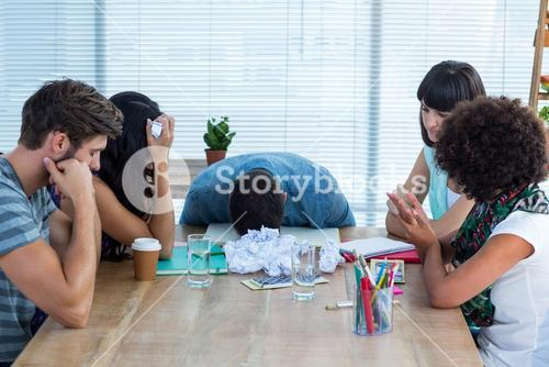 Exhausted creative business team in meeting