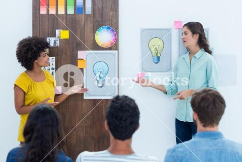Casual young businesswoman giving presentation to colleagues