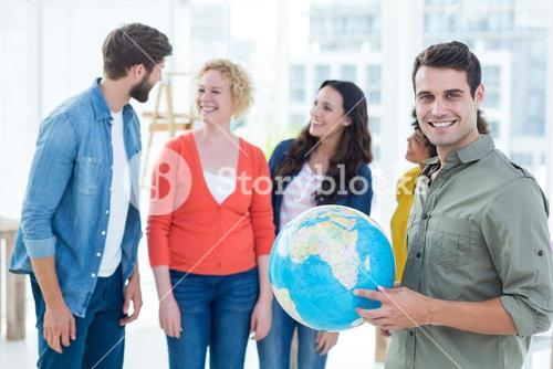 Young creative business people with a globe