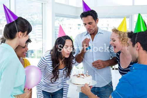 Businesswoman blowing candles on her birthday cake