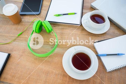 Overhead of coffee and headphone on the desk
