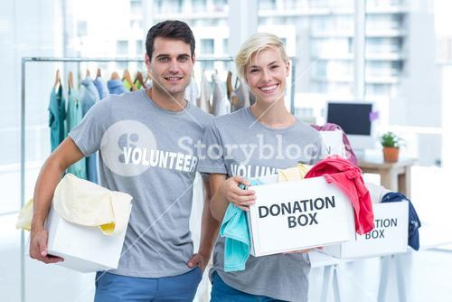 Volunteer couple holding donation boxes