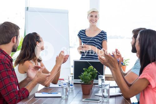Colleagues clapping hands in a meeting