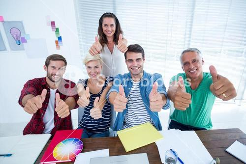 Creative business team gesturing thumbs up in meeting