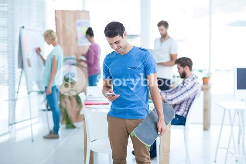 Businessman holding a skateboard in the office