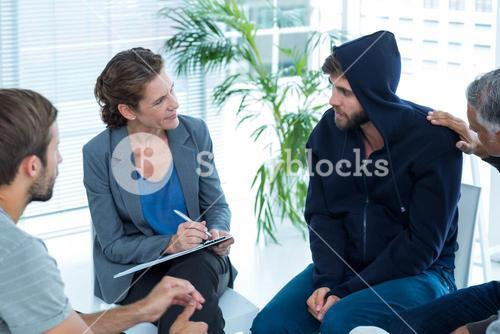 Concerned man comforting another in rehab group