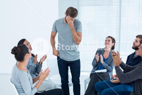Rehab group applauding delighted man standing up