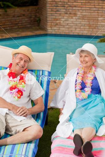 Senior couple lying down beside the swimming pool