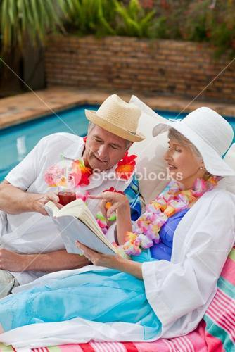 Mature woman reading a book while her husband is drinking a cocktail