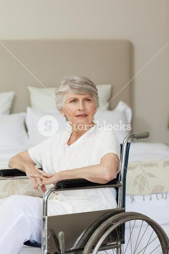 Concentrated senior woman in her wheelchair at home