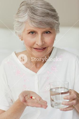 Senior woman with pills in her palm