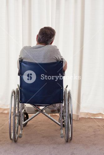 Mature man in his wheelchair with his back to the camera