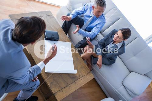 Angry business people speaking together on couch