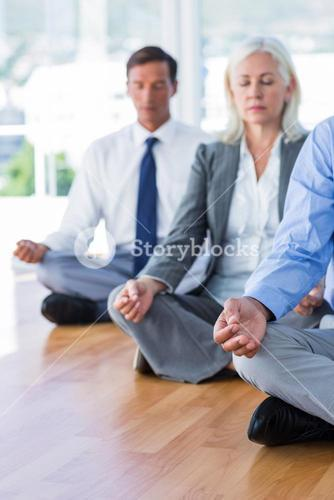 Business people doing yoga on floor