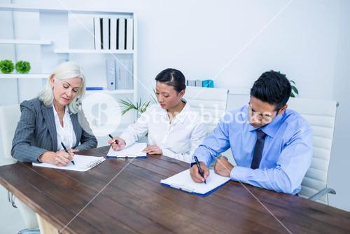 Business people writing on clipboards