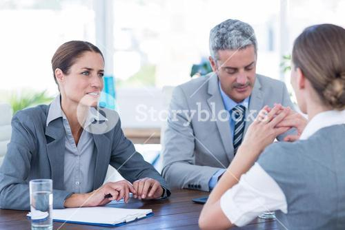 Business people interviewing young businesswoman