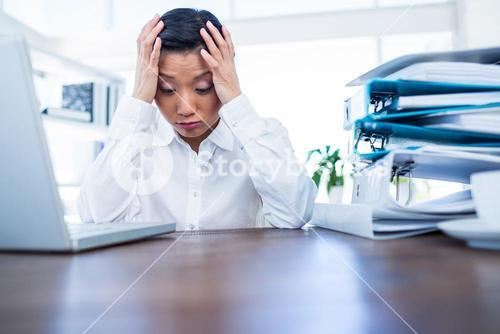 Depressed businesswoman with hands on head