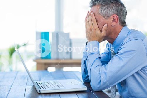 Irritated businessman with hands on head
