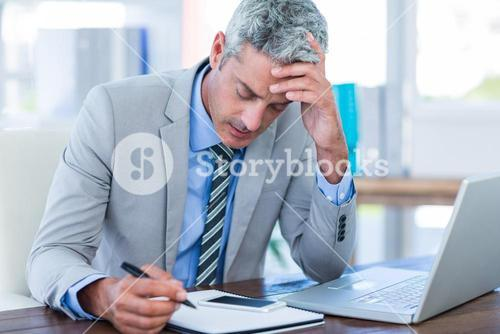 Irritated businessman trying to work