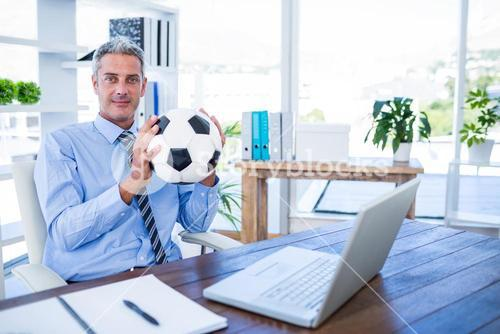 Happy businessman looking at camera and holding foot ball