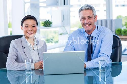 Happy business people working on laptop computer