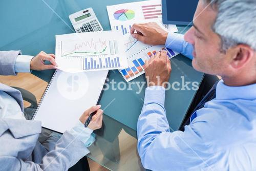 Business people looking at documents with graphics