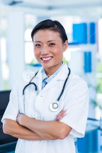 Confident doctor with arms crossed smiling at camera