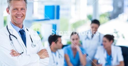 Doctor smiling at camera with colleagues behind