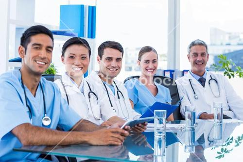 Happy doctors looking at camera while sitting at a table