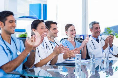 Doctors applauding while sitting at a table