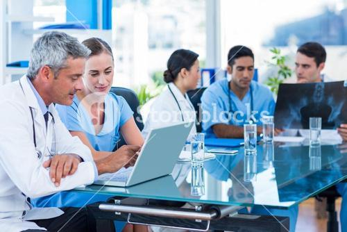 Doctor and nurse looking at laptop with colleagues behind