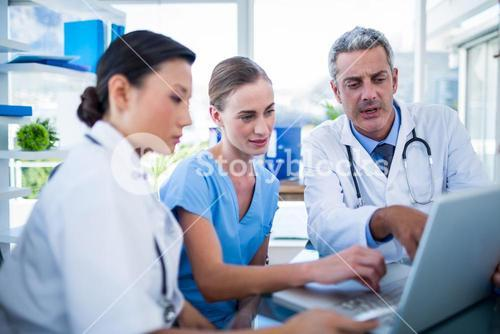 Doctors and nurse looking at laptop