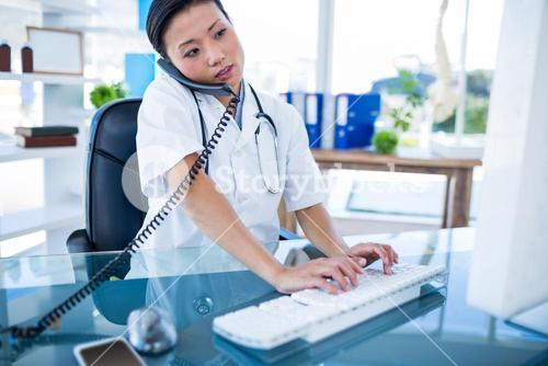 Doctor having phone call and using her computer