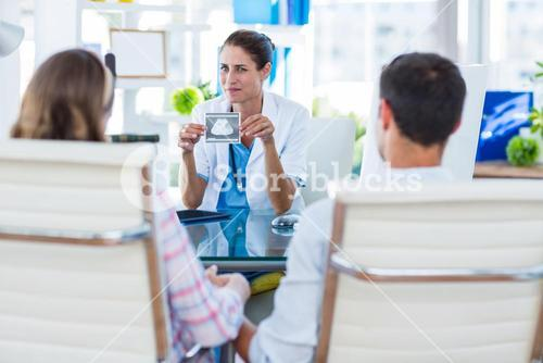 Doctor showing sonagram to couple