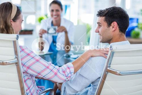 Rear view of pregnant woman and her husband discussing with doctor