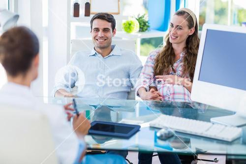 Pregnant woman and her husband discussing with doctor