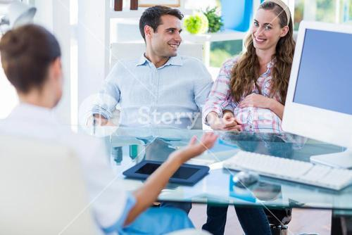 Pregnant woman with her husband smiling at camera
