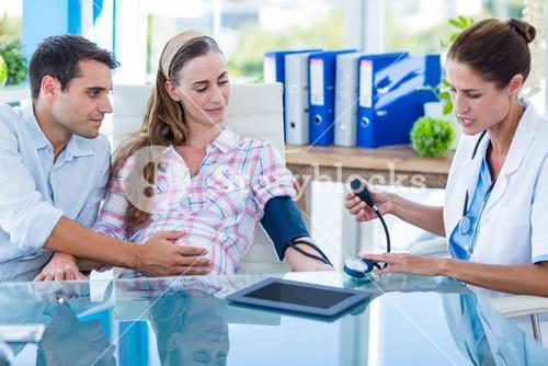 Doctor taking the blood pressure of a pregnant patient with her husband