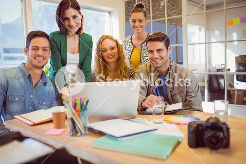 Portrait of smiling casual colleagues using computer